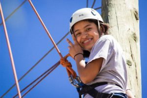 Girl smiles while attached to rope in climbing gear