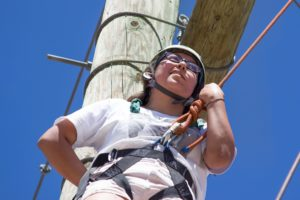 Girl looks up while attached to rope in climbing gear