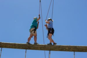 Campers meet in the middle of balance beam in climbing gear