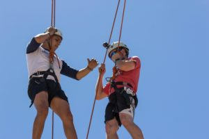 Two men balance on beam attached to climbing gear
