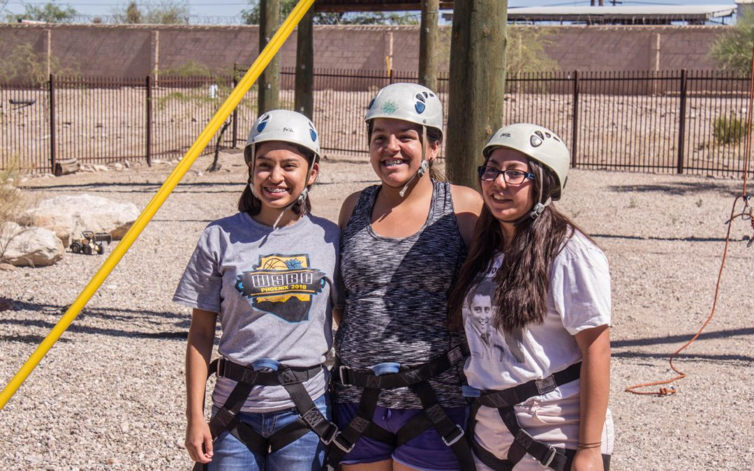 Three girls smile for picture with climbing gear