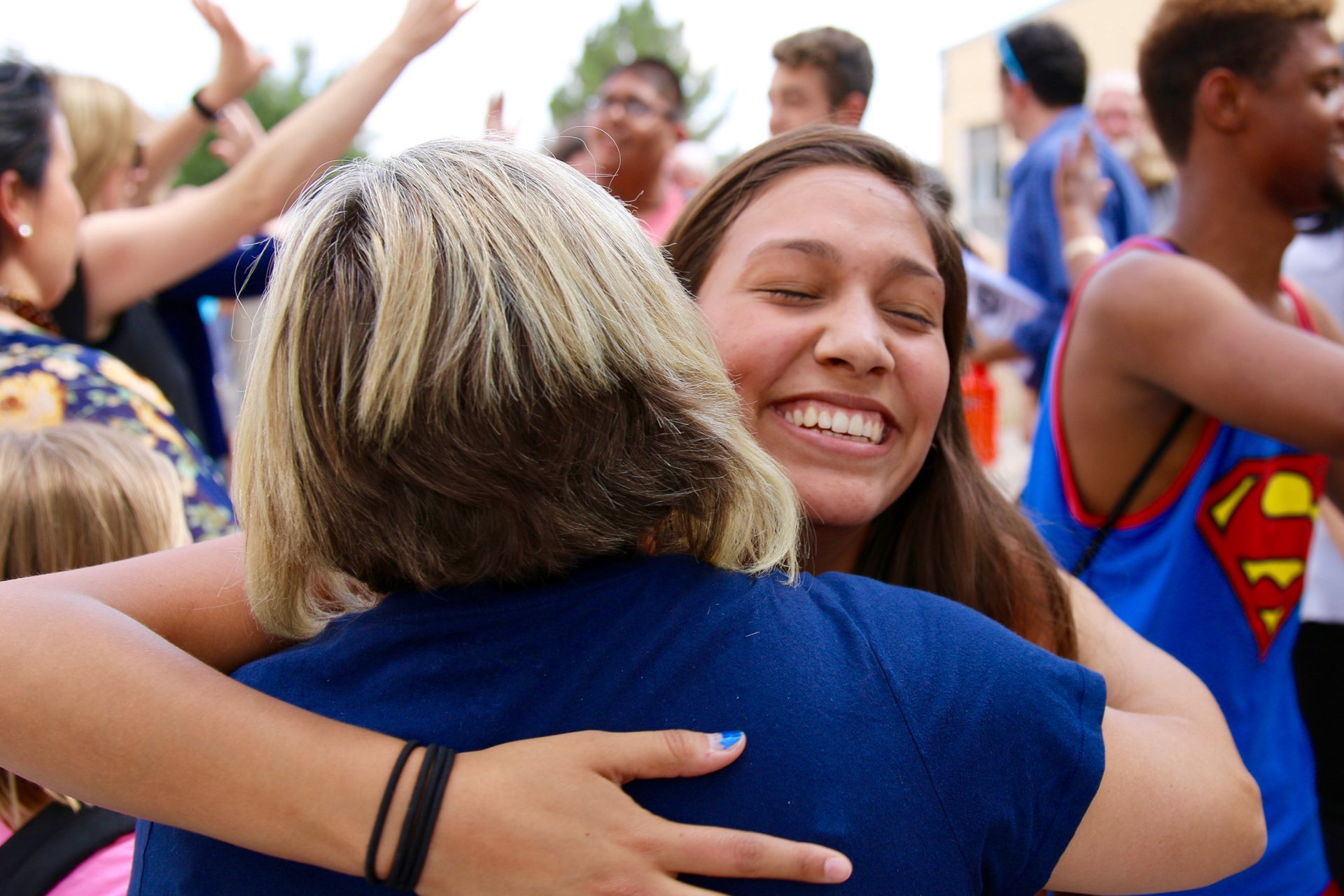 Student hugs staff member during the 2016 bus farewell.