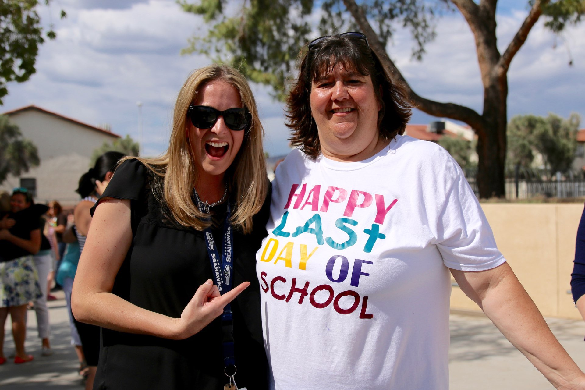 Staff members smile at camera during the 2016 PDSD bus farewell.