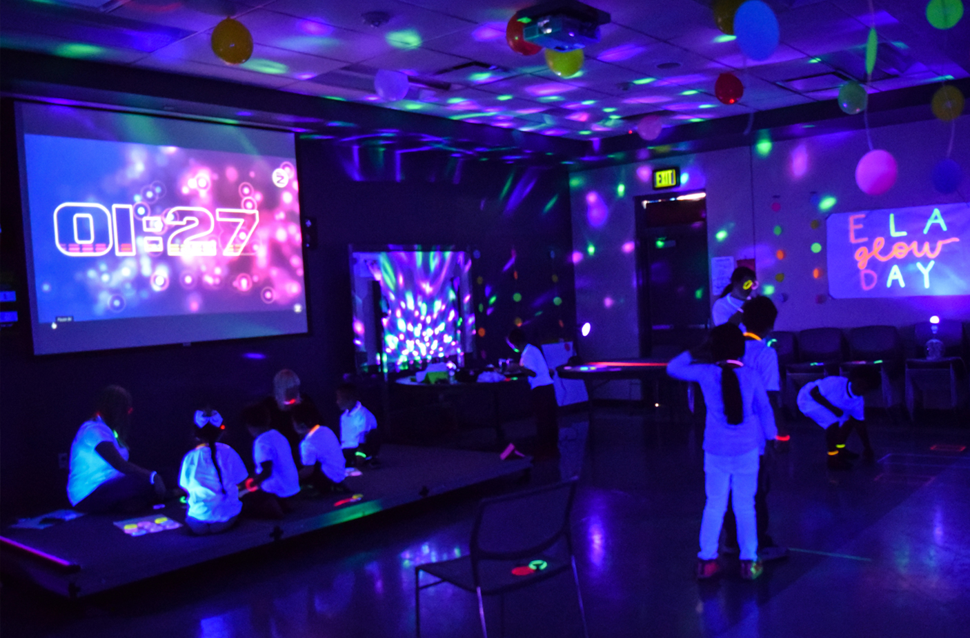 We see multiple lights in dark room on the wall, ceiling and floor. We can see some students sitting on the floor and some are standing. Their white shirts and pants are glowing that are reflected from blacklights.
