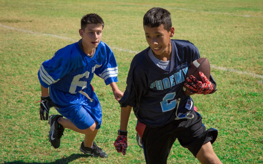A PDSD flag football player runs with the ball away from another player in blue