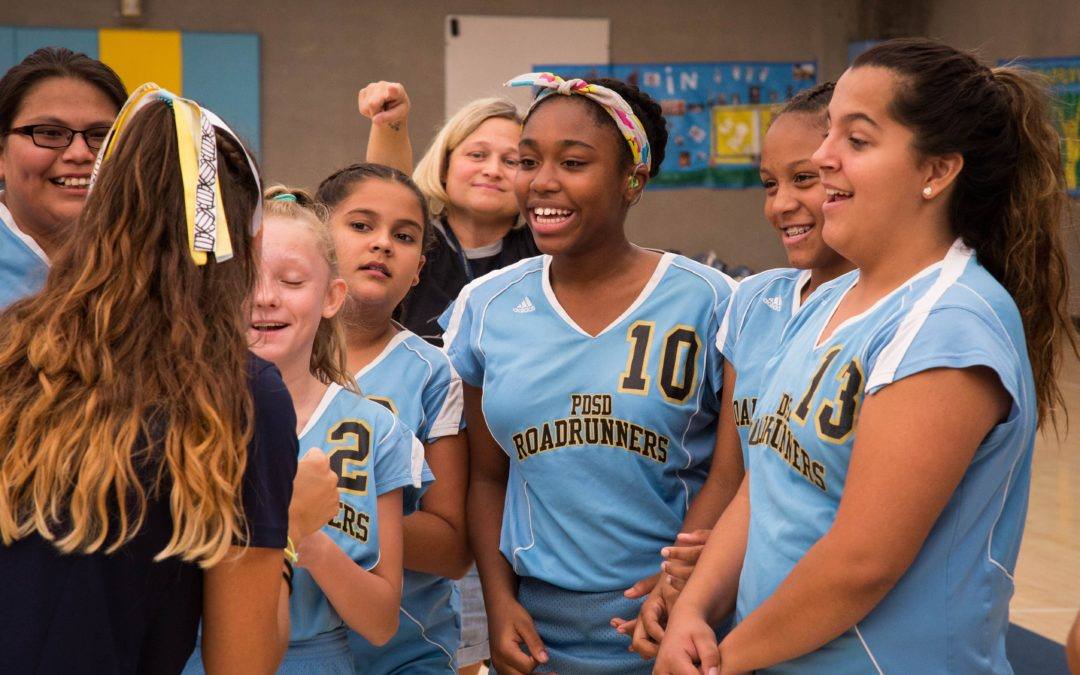 The PDSD girl's volleyball team smiles at their coach as she speaks.