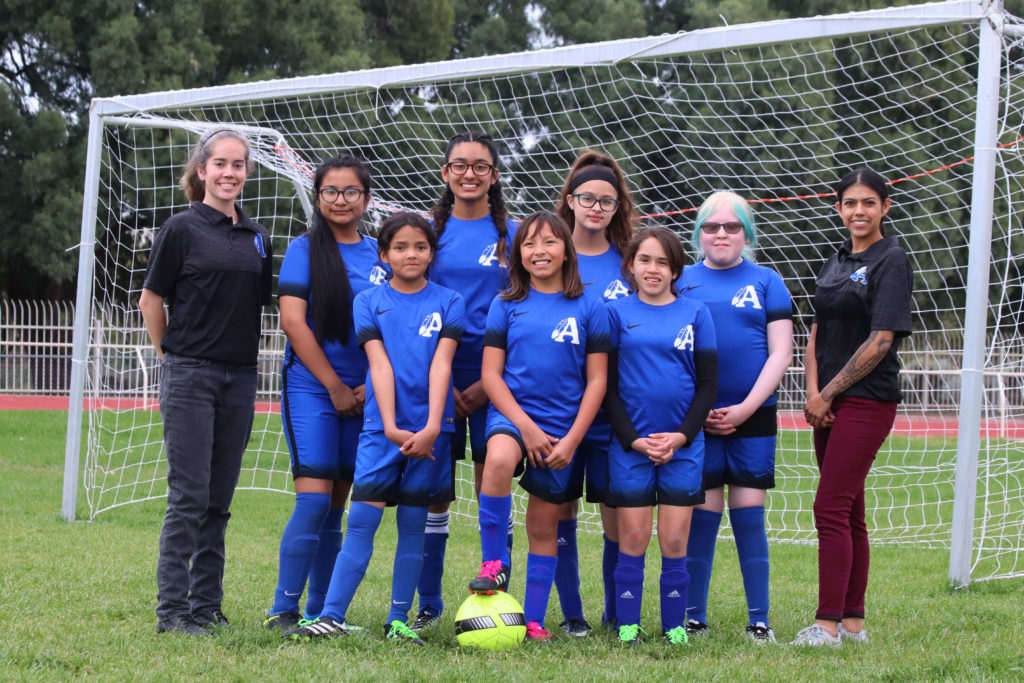 a group of middle schools girls pose for a portrait with their coaches in front of the soccer goal