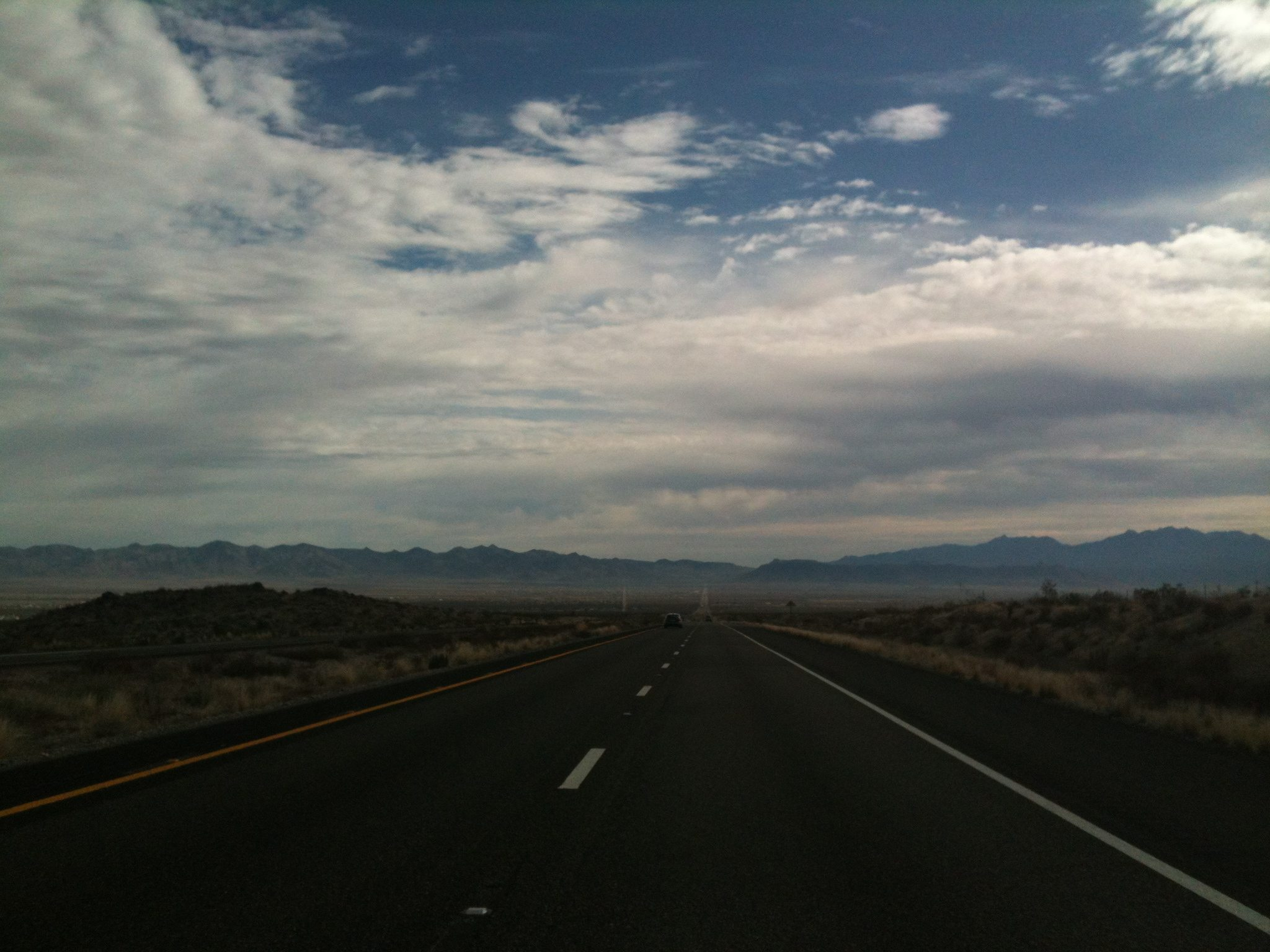 Highway in the desert with blue sky and clouds