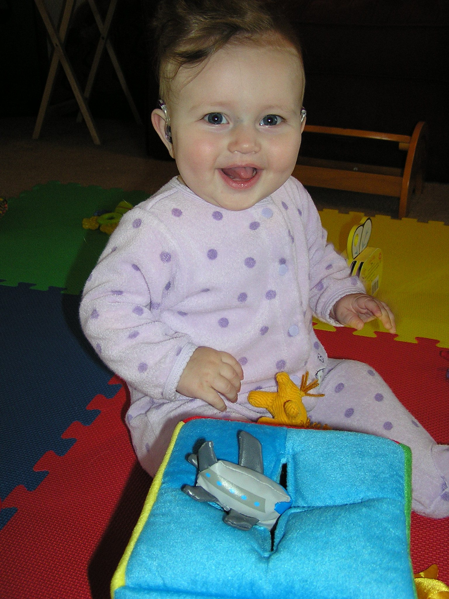 Baby smiling and playing with airplane book