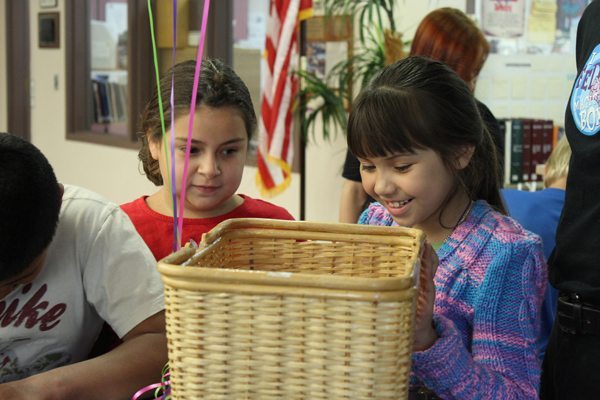Two young ASB students peer into a wicker basket. One of the girls is smiling.