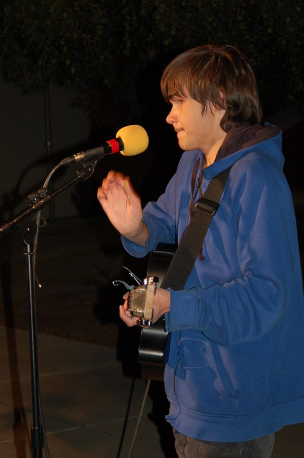 ASB HS student is playing a guitar while standing front of a microphone. He is reaching for the microphone with his right hand.
