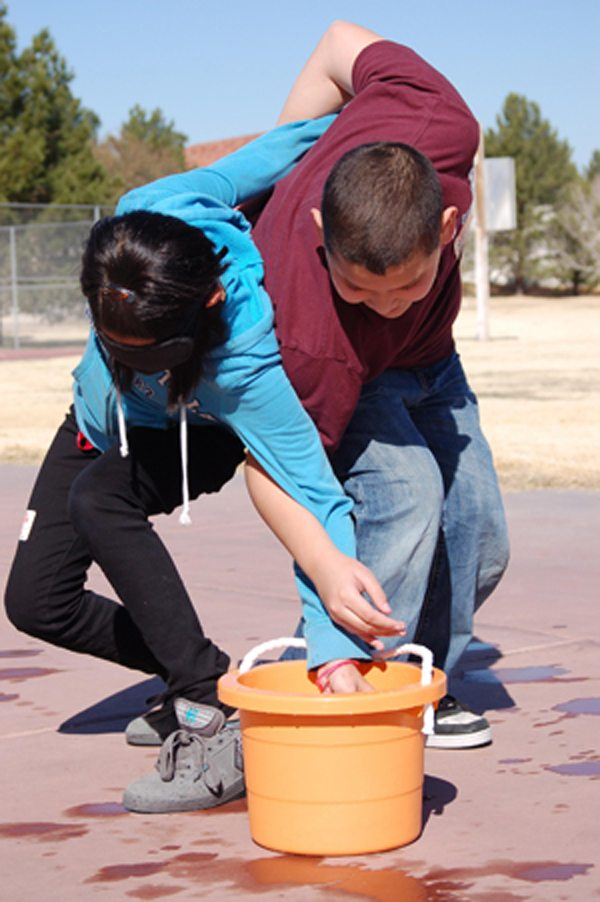 Two students, one blindfolded, work together to retrieve an object from a bucket of water outside the gym on a sunny day. This is an exercise in teamwork and cooperation. They have their arms interlocked and must move as one when only one student can see where the bucket is located.
