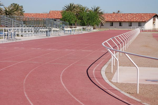 The ASDB athletic track and football field with handrail guide on the inner lane to assist VI students. To the left are bleachers and in the background are single story ASDB buildings with red tile roofs.