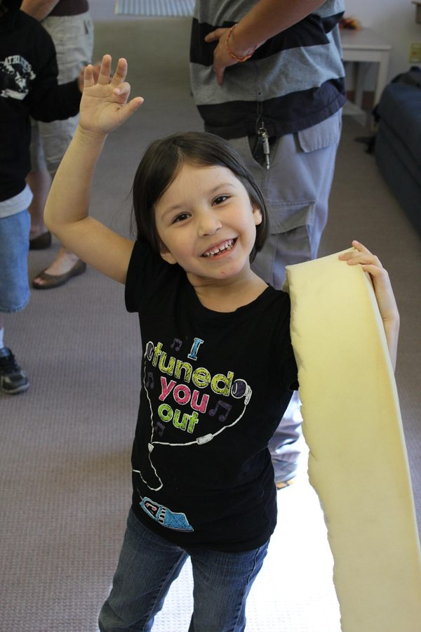 A young ASDB student is waving to the camera. She is holding a long piece of foam rubber used in a presentation in the other hand.