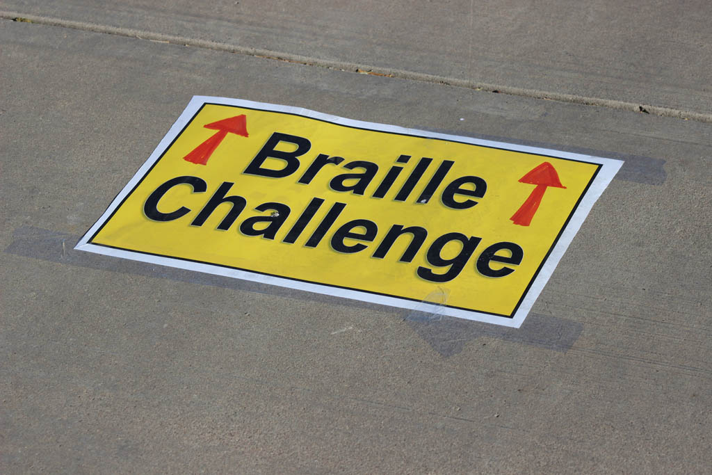 Braille Challenge text poster taped to floor pointing to the 2016 Braille Challenge Festivities