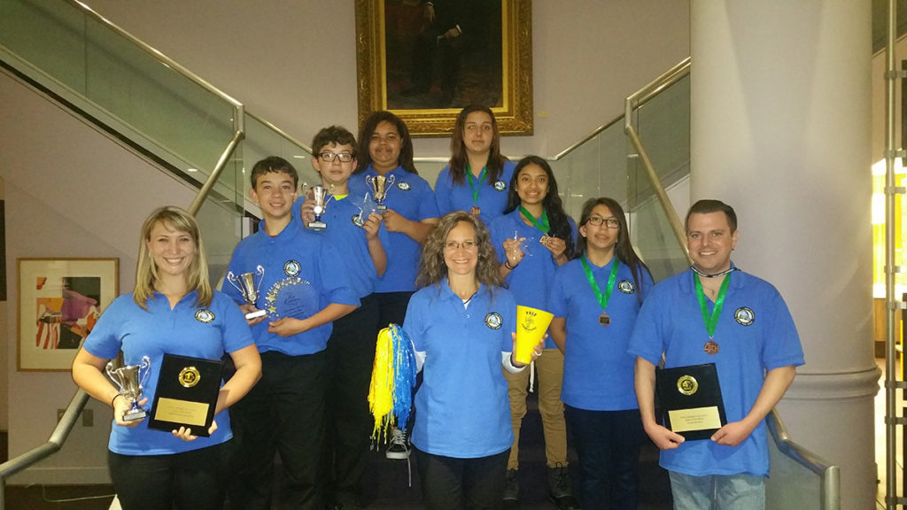 Picture of students and teacher standing on a stairwell holding their Battle of the Books awards