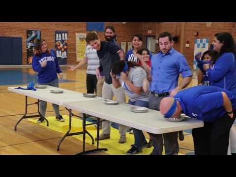 An image still from the ASDB Homecoming Pep Rally showing staff participating in a pie eating contest.