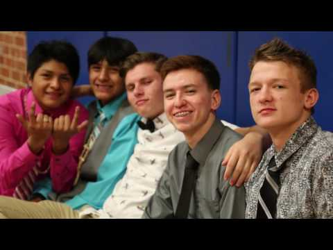 Student Basketball players dressed up smiling at the camera.