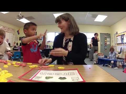 An image still from the Reichman PDSD Kindergarten Class Visit video that shows Annette Reichman interacting with students at a desk.