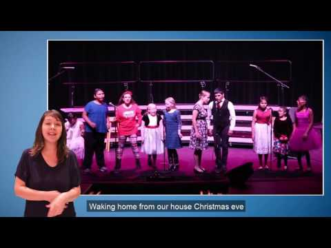 An image still from the Grandma Got Run Over by a Reindeer video showing students on stage performing with an ASL interpreter.