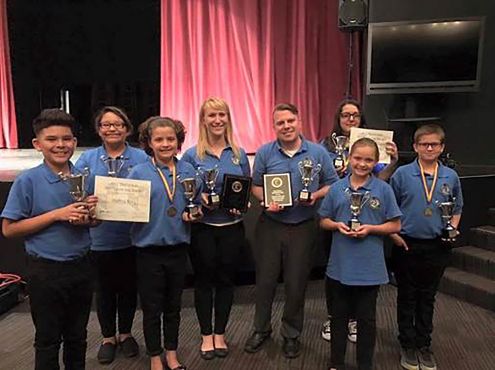 Six PDSD middle school students and two adult chaperones smiling for the camera and holding silver (representing second place in nationals) trophies.