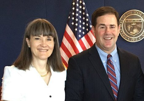Photo of Annette Reichman and Governor Doug Ducey standing in front of the US flag and state seal smiling at the camera