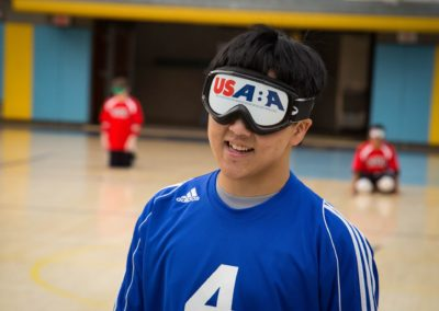 ASB goalball player smiles at the camera while wearing player goggles