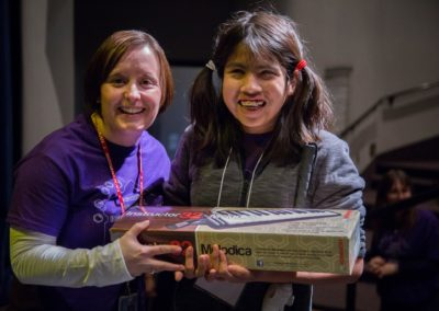 An ASB student wins a melodica and smiles with principal Kelly Creasy