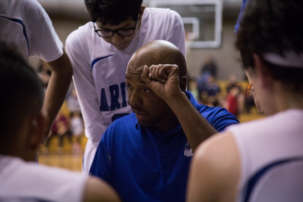 Gerald Brown instructs the ASD boys basketball team during a huddle