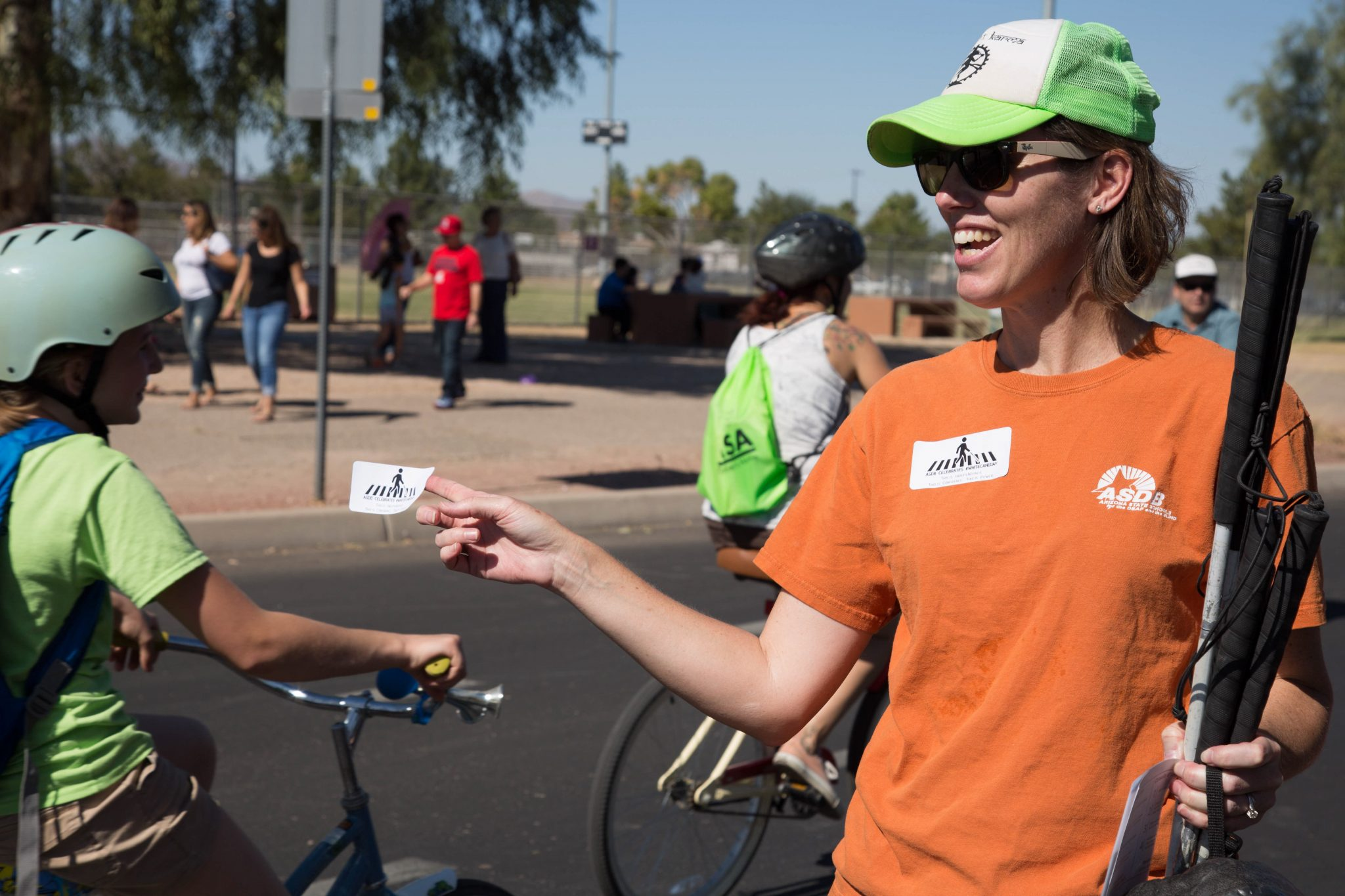 A volunteer hands out a race badge