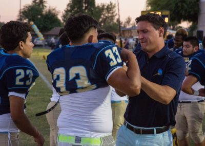 PDSD football coach helps a player with their uniform
