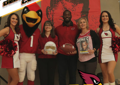 Derrick Coleman poses for a photo with Superintendent Annette Reichman, PDSD Principal Courtney Fritz, two cheerleaders and the Cardinals mascot