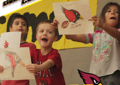 Three PDSd students hold up signs with cardinals