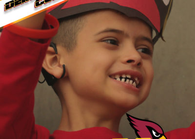 A PDSD student with a cardinals hat on smiles