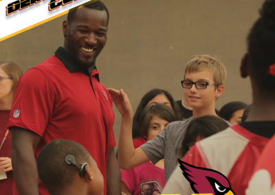 Derrick Coleman smiles and interacts with a child