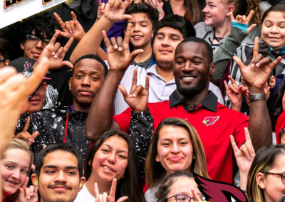 """Derrick Coleman poses for a picture with PDSD students. THey are holding up the ASL sign for """"i love you."""""""