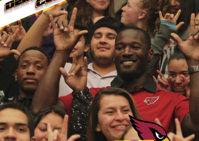 """Derrick Coleman poses for a portrait with PDSD students holding up the ASL sign for """"I love you"""""""