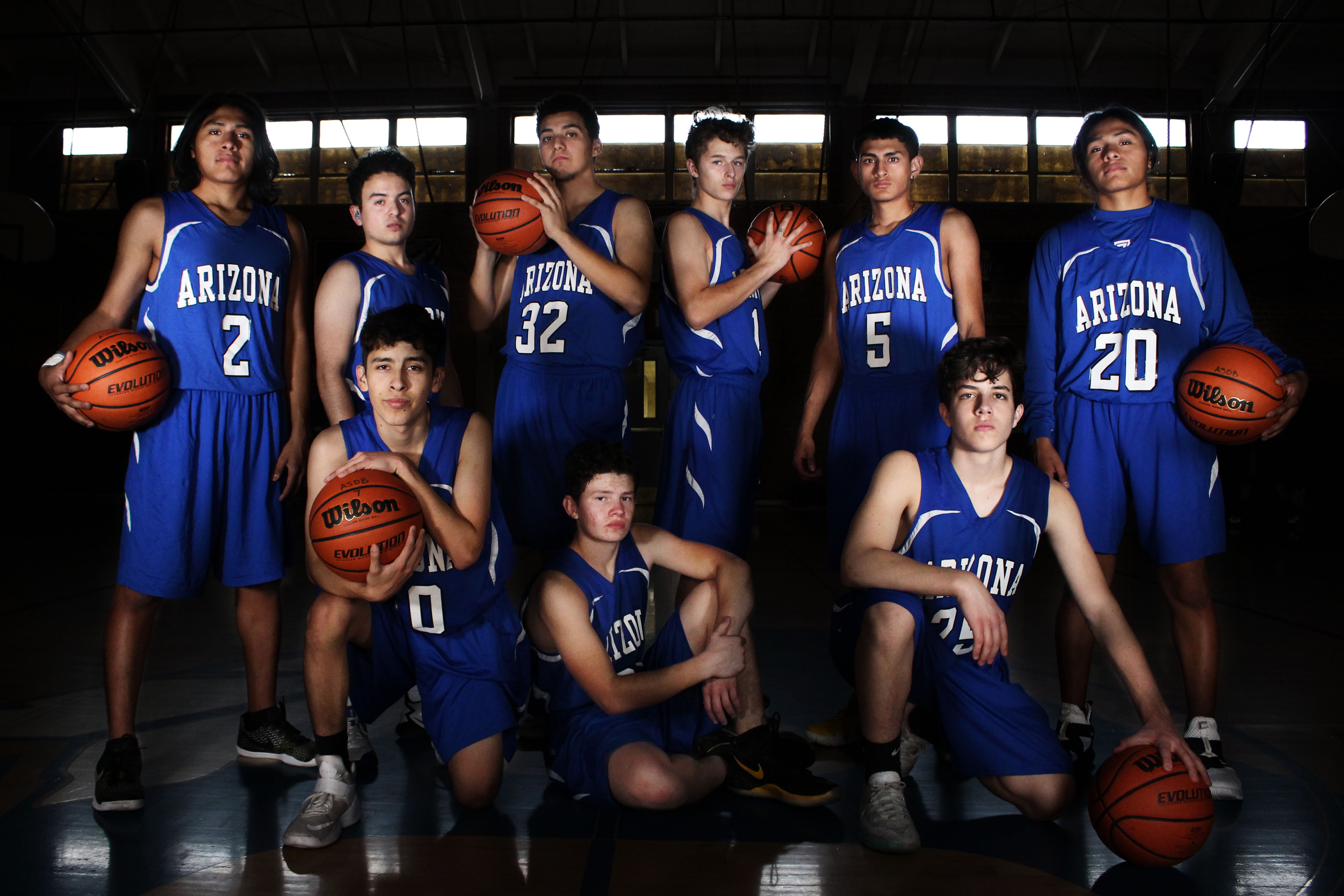 A dramatic portrait of the ASDB Boys' Basketball Team 2018-2019. Nine boys look serious at the camera holding basketballs.