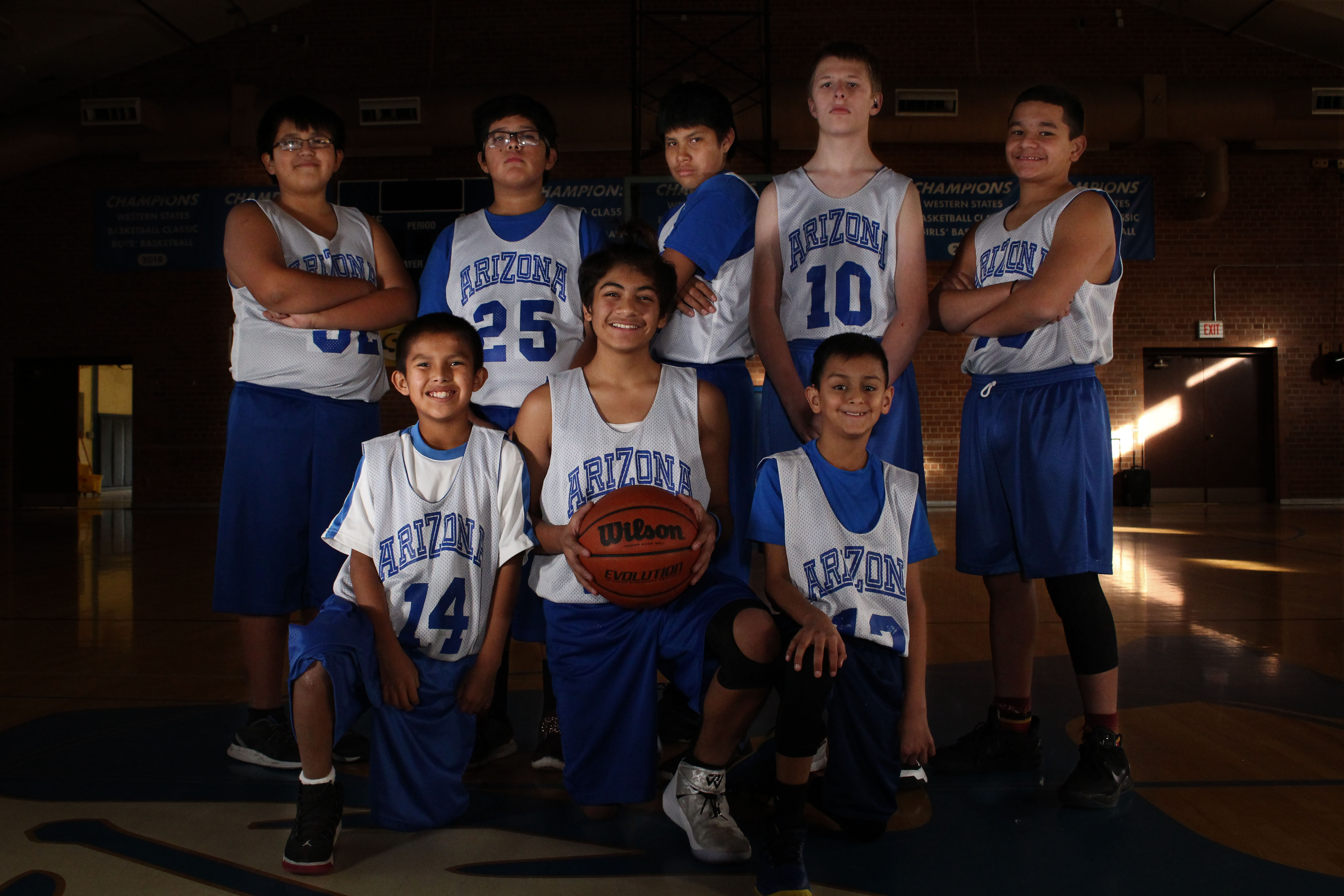 A dramatic portrait of the ASDB Middle School Boys' Basketball Team 2018-2019. They are smiling while one boy in the middle holds a basketball.