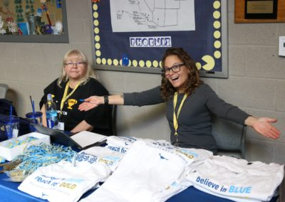 Two women pose at a table with PDSD shirts