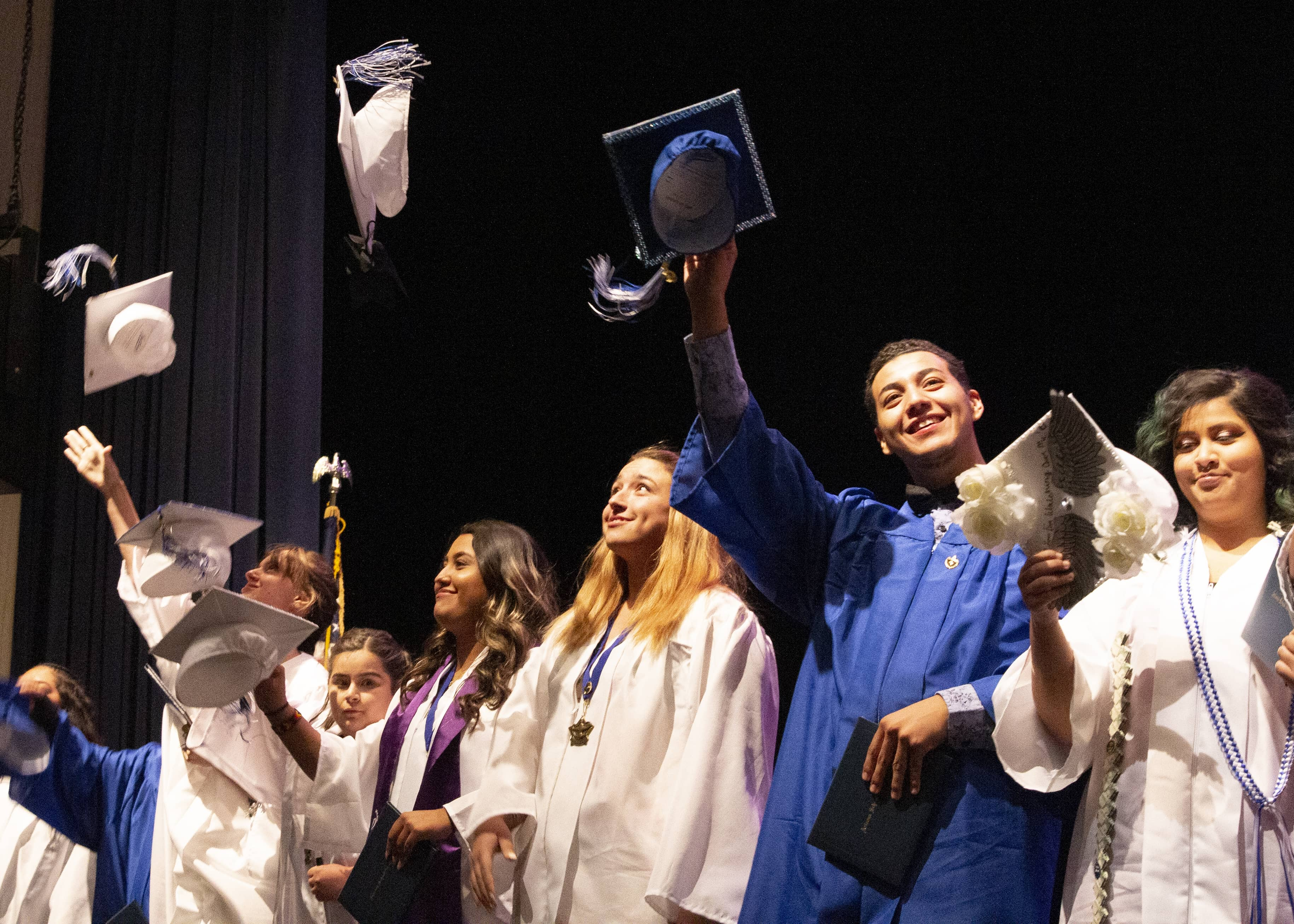 Students wearing cap and gowns wave in the air during graduation